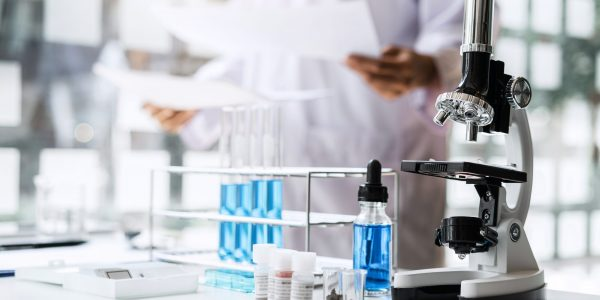 Biochemistry laboratory research, Chemist is analyzing sample in laboratory with Microscope equipment and science experiments glassware containing chemical liquid.